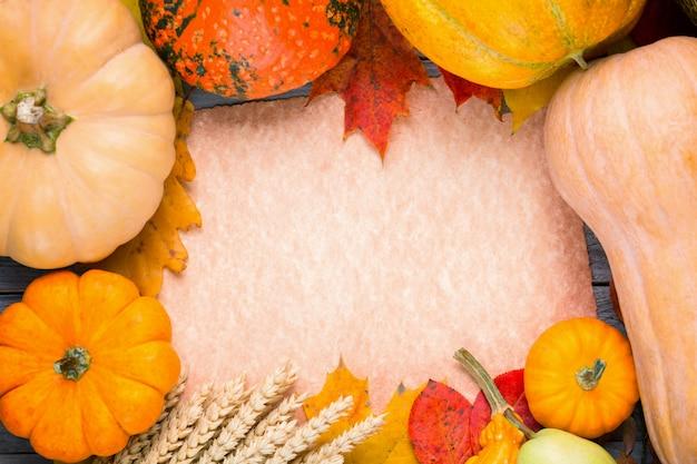Fundo de ação de graças outono com abóboras, centeio, melão, maçã, pêra e folhagem colorida em papel vintage. vista superior com espaço de cópia para o seu texto
