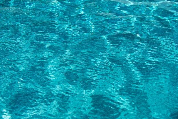 Fundo de água azul na piscina com reflexão do sol ondulação das ondas de água na piscina de águas claras ...