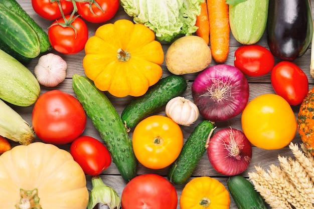 Fundo de alimentos orgânicos vegetais frescos. vegetais de outono e tema do dia de ação de graças. abóbora, cebola, cenoura, tomate, cogumelo, pepino e outros.