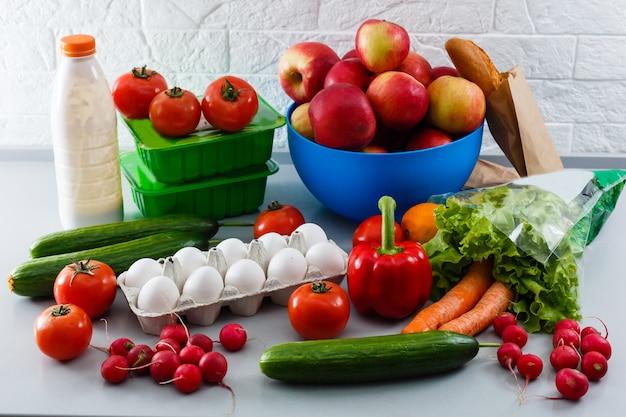 Fundo de alimentos saudáveis, legumes, frutas, ovos e produtos lácteos na mesa branca, vista superior