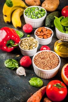 Fundo de alimentos saudáveis, produtos de dieta alcalina na moda - frutas, legumes, cereais, nozes. óleos, espaço de cópia de fundo concreto azul escuro