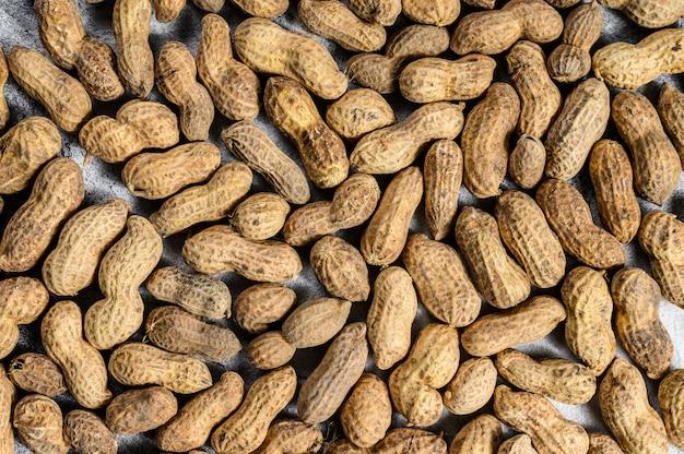 Fundo de amendoins crus, textura, vista superior, espaço para texto
