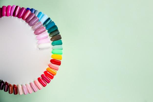 Fundo de amostras de esmaltes multicoloridos. vista superior da paleta de cores dos serviços de unhas no salão de beleza. manicure da moda. verniz em gel. foco seletivo. copie o espaço.
