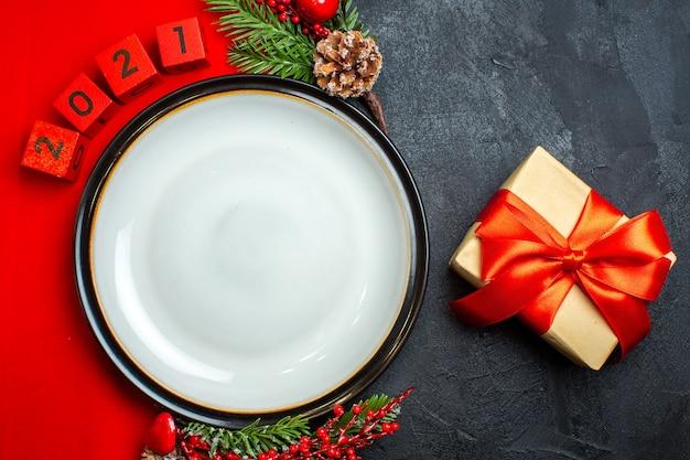Fundo de ano novo com acessórios de decoração de prato de jantar ramos de abeto e números e presente em um guardanapo vermelho sobre uma mesa preta