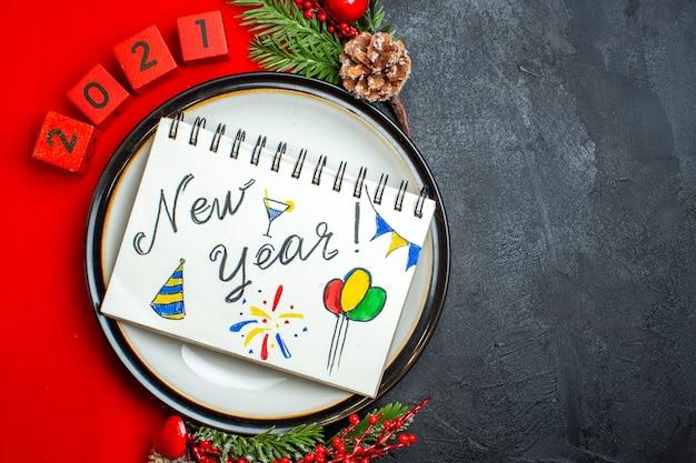 Fundo de ano novo com caderno com desenhos de ano novo em um prato de jantar decoração acessórios ramos de abeto e números em um guardanapo vermelho sobre uma mesa preta