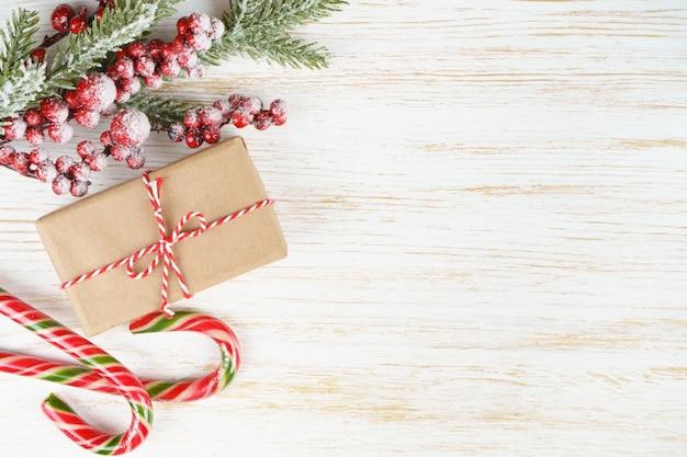 Fundo de ano novo com doces de galho de árvore de natal e caixa de presente