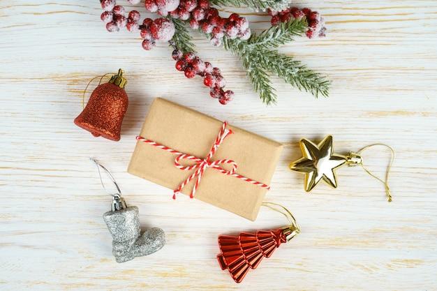 Fundo de ano novo com galho de árvore de natal, árvore do abeto decorativo, cones de abeto e caixa de presente em fundo branco de madeira com espaço para texto. camada plana, vista superior.