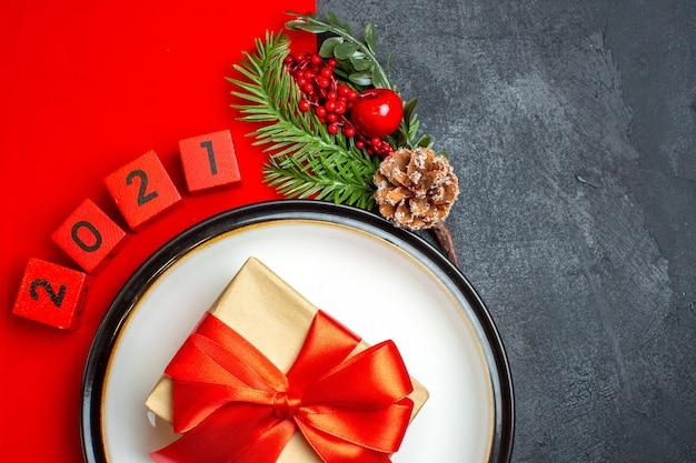 Fundo de ano novo com lindo presente em um prato de jantar acessórios de decoração ramos de abeto e números em um guardanapo vermelho em uma mesa preta meia foto tirada