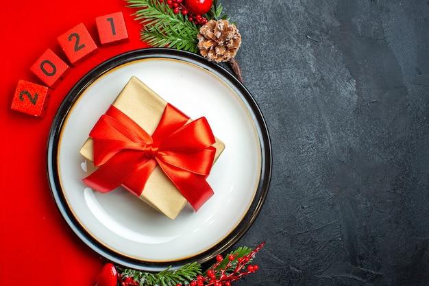 Fundo de ano novo com lindo presente em um prato de jantar acessórios de decoração ramos de abeto e números em um guardanapo vermelho em uma mesa preta