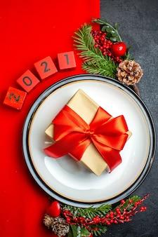 Fundo de ano novo com lindo presente em um prato de jantar acessórios de decoração ramos de abeto e números em um guardanapo vermelho em uma vista vertical de mesa preta