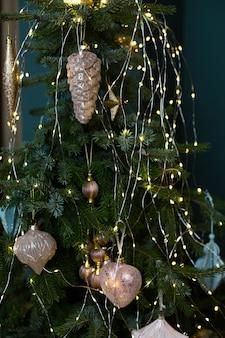 Fundo de ano novo e natal com galhos de pinheiro, guirlanda e decoração de cones dourados