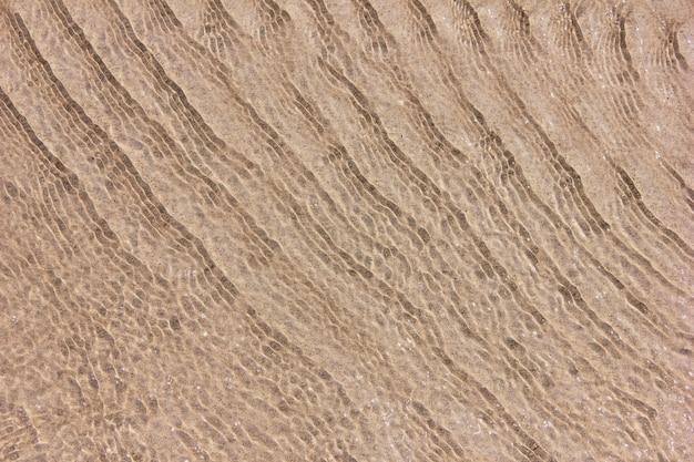 Fundo de areia através da água do mar claro.