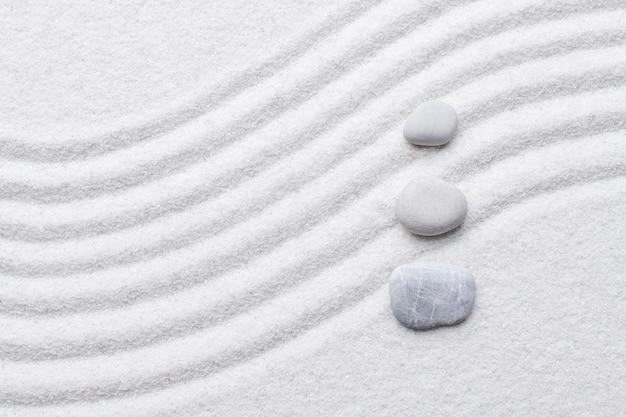 Fundo de areia branca de pedras zen na arte do conceito de equilíbrio