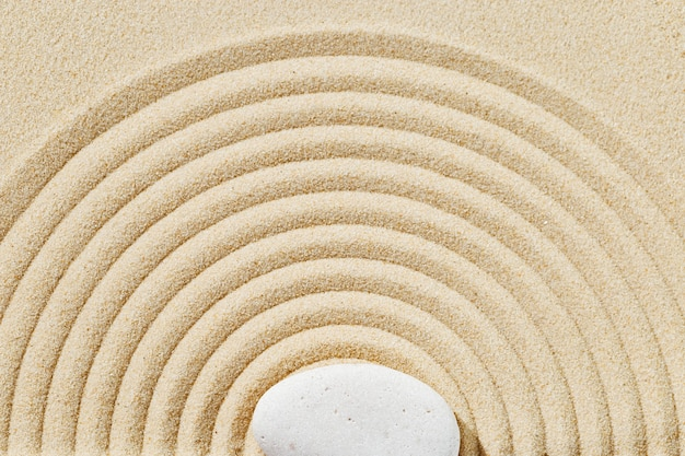 Fundo de areia para meditação no jardim zen com monte de pedras e linhas redondas na areia