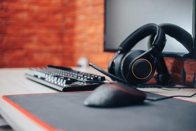 Fundo de arena de jogos com computador de fones de ouvido de engrenagem do mouse, focalizar em fones de ouvido selecionado
