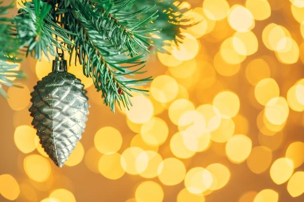 Fundo de árvore de natal com bugiganga cinza sobre bokeh dourado espumante