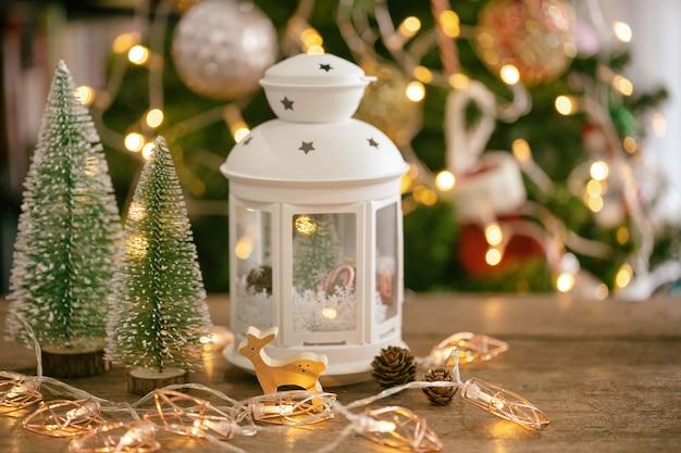Fundo de árvore de natal com lanterna, folhas de pinheiro, pinhas e renas de madeira bugiganga.