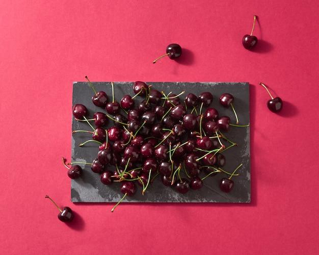 Fundo de bagas de verão de cerejas vermelhas maduras na placa de pedra escura sobre fundo vermelho, com lugar para texto.