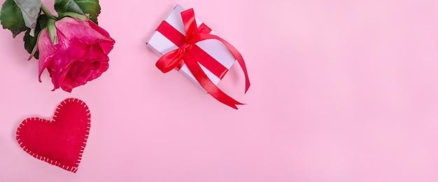 Fundo de banner de dia dos namorados. rosa vermelha com coração vermelho e um presente em um fundo rosa com espaço de cópia.