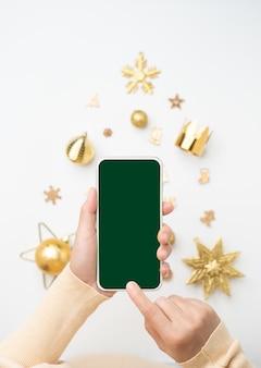 Fundo de banner de natal. mulher furando celular com tela em branco sobre o natal dourado na árvore de natal