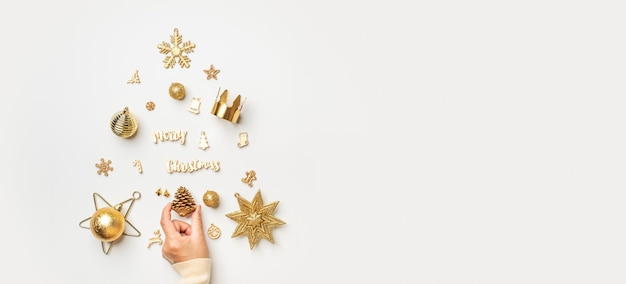 Fundo de banner de natal. mulher mão decoração de cor dourada itens de natal na árvore de natal