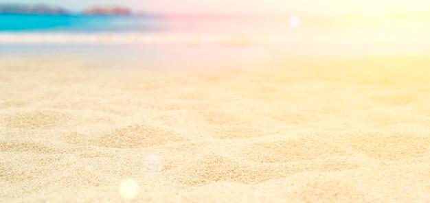 Fundo de banner de praia. praia turva e ensolarada com areia e mar. conceito de férias, relaxamento e viagens tropicais. foto de alta qualidade