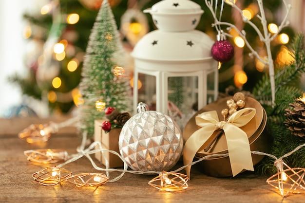 Fundo de bokeh de natal com caixa de presente de natal, lanterna, pisca-pisca estrela, bugiganga e pinhas.