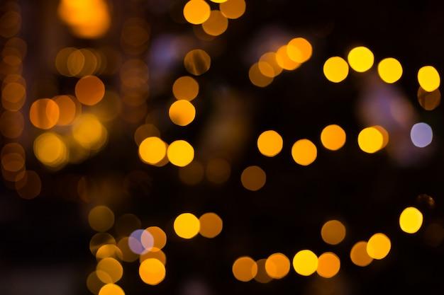 Fundo de bolas amarelas bokeh. pano de fundo brilhante feriado dourado. fundo desfocado com estrelas piscando.