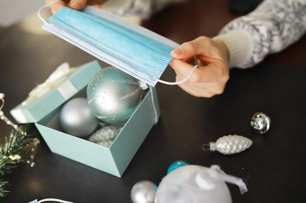 Fundo de bolas de natal e máscaras protetoras médicas. o ano novo de 2021 está chegando. conceito de ano novo e coronavírus. copie o espaço.
