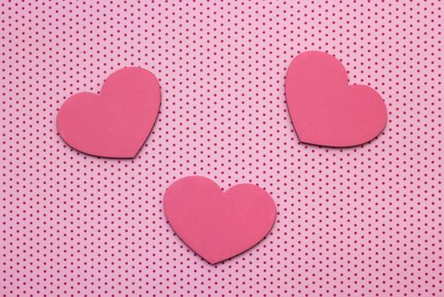 Fundo de bolinhas rosa e corações de madeira