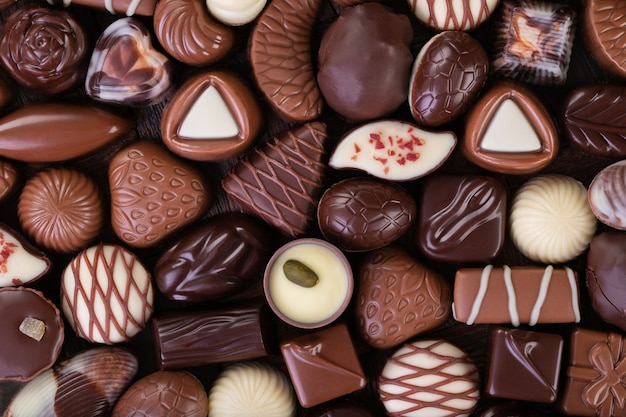 Fundo de bombons de chocolate, sobremesa doce como pano de fundo, vista superior.