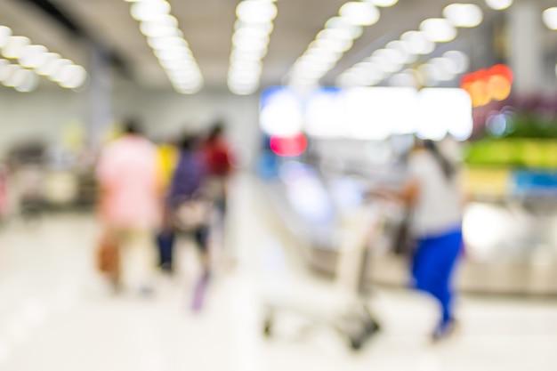 Fundo de borrão: avião de passageiros aguardando saco na reivindicação de bagagem com luz bokeh