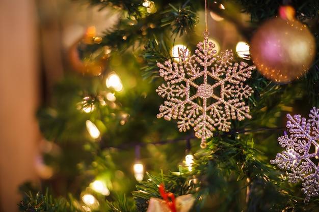 Fundo de brilho de prata festivo de suspensão da quinquilharia do floco de neve com a árvore de natal verde decorada no shopping.