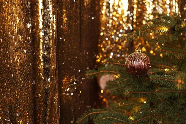 Fundo de brilho escuro de natal com decorações luxuosas douradas e luzes festivas. árvore de natal.