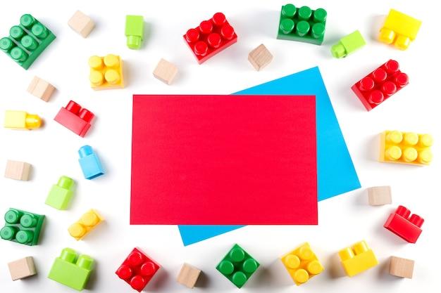 Fundo de brinquedos. cubos coloridos e blocos de construção com cartão de papel em branco vermelho sobre fundo branco