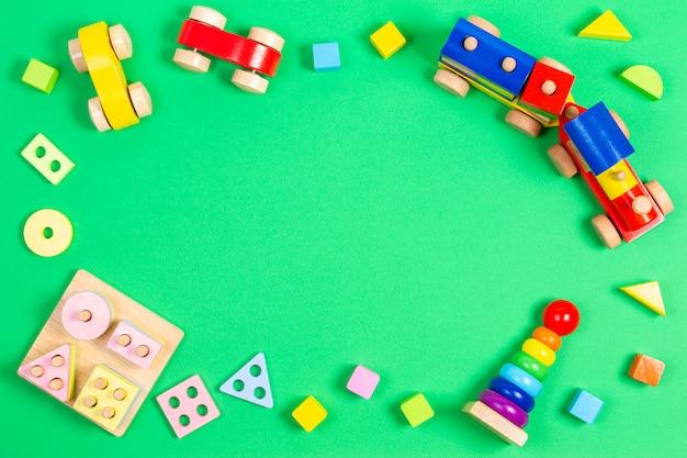 Fundo de brinquedos de crianças bebê. brinquedo educacional de madeira de empilhamento geométrico, trem de madeira, carros, torre de pirâmide de empilhamento e blocos coloridos sobre fundo verde