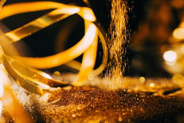 Fundo de cachoeira brilhante glitter dourados. conceito de arte do prego e materiais de maquiagem