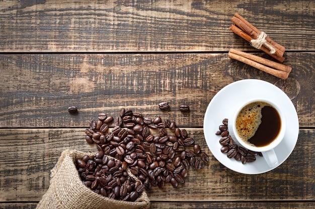 Fundo de café com espaço de cópia. xícara de café, feijão, paus de canela em um fundo de madeira. vista superior, configuração plana.