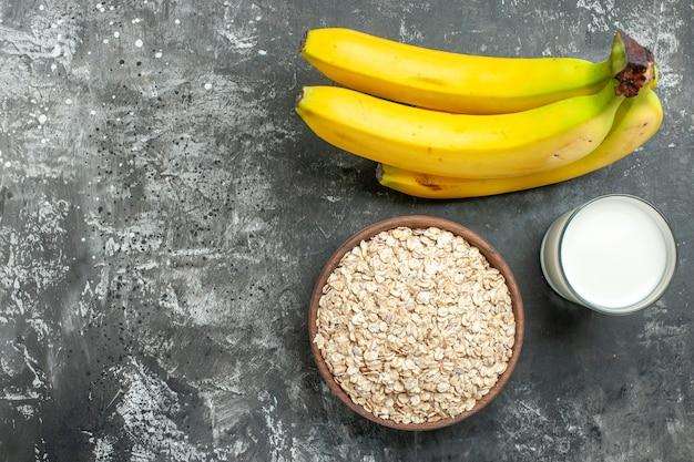 Fundo de café da manhã com farelo de aveia orgânica em uma panela de leite de madeira marrom em um pacote de bananas de vidro em fundo escuro