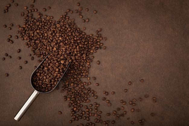 Fundo de café. grãos de café e colher em fundo marrom. espaço de cópia da vista superior
