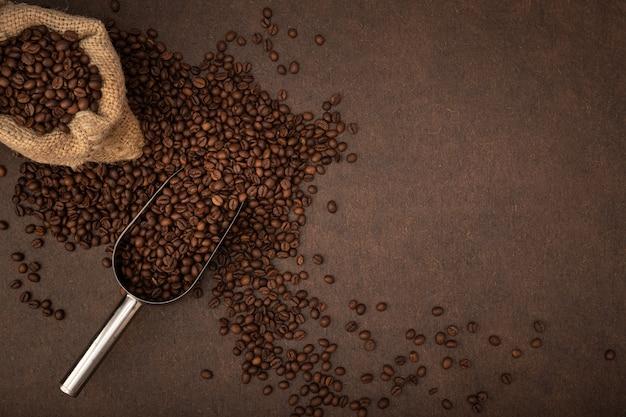 Fundo de café. grãos de café, saco e colher em fundo marrom. espaço de cópia da vista superior