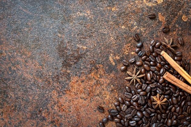 Fundo de café. grãos de café torrados, paus de canela, anis estrelado espalhados sobre a mesa com espaço de cópia. vista superior, configuração plana.