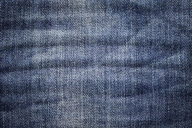 Fundo de calça jeans escura. textura denim clássico. superfície de roupas da moda.