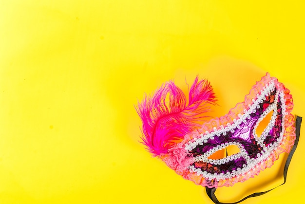 Fundo de carnaval com máscara de férias em fundo amarelo brilhante
