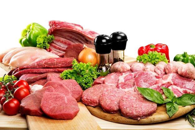 Fundo de carne crua fresca com legumes na mesa de madeira, isolado no fundo branco