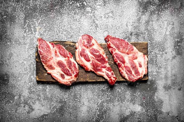 Fundo de carne crua. pedaços crus de bife em uma velha tábua de corte. sobre uma mesa rústica.