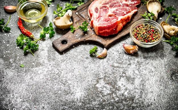 Fundo de carne crua. um pedaço de costeletas de porco crus com especiarias perfumadas e ervas frescas. sobre fundo rústico.