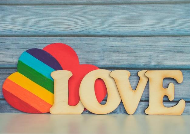 Fundo de cartão de dia dos namorados, coração bonito arco-íris como uma bandeira de arco-íris de orgulho lgbt com coração de papel vermelho e palavra de madeira decorativa. dia dos namorados romântico. amo os direitos humanos e o conceito de liberdade.