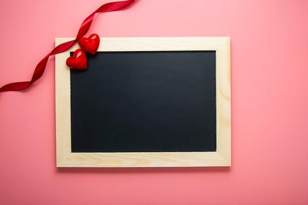 Fundo de cartão de dia dos namorados. corações e fita vermelha no quadro de lousa
