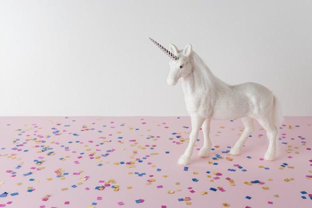 Fundo de celebração colorido com vários confetes de festa e unicórnio de purpurina